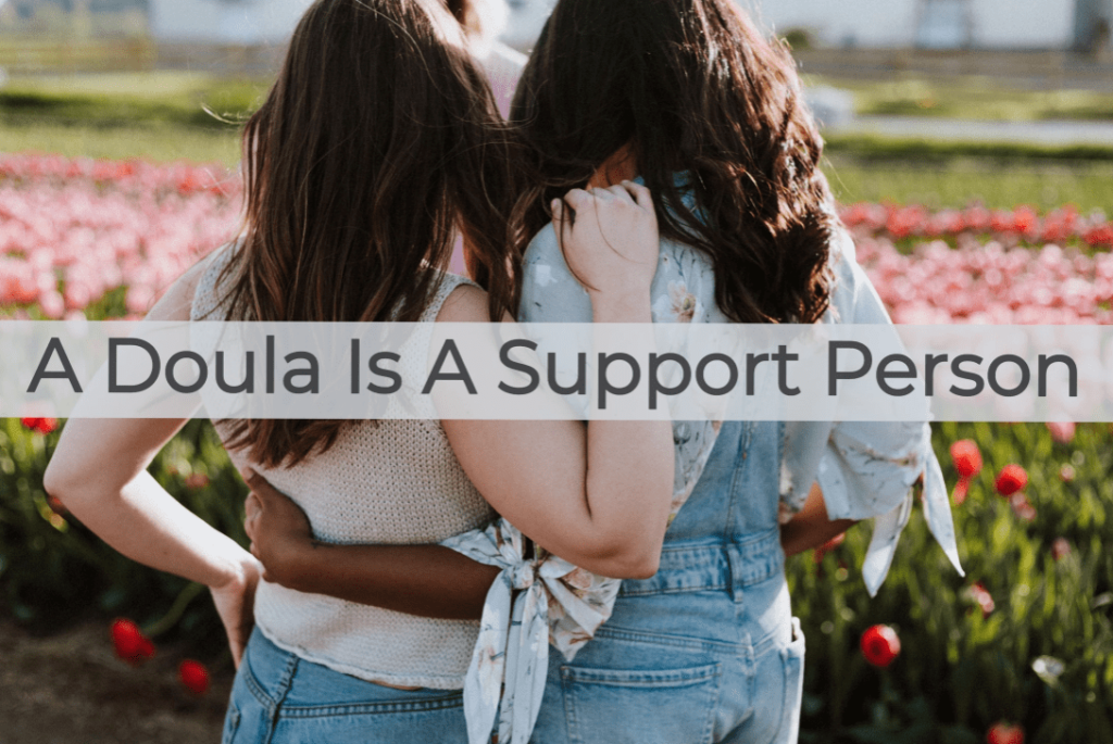 Doulas supporting each other outside in a bed of flowers